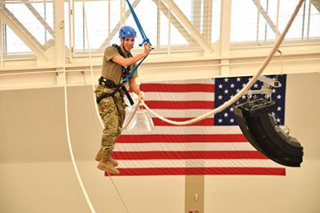 ROTC cadet walking the ropes course, with the American flag in the background