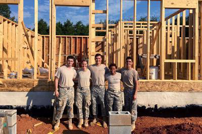 A group of cadets stand in front of the wooden-frame of a house