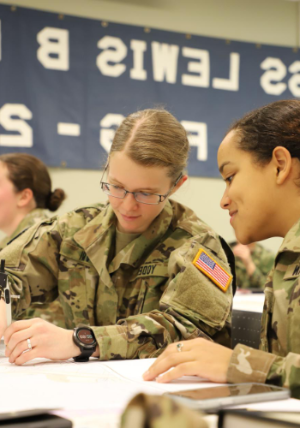 Two female NROTC cadets working on a project