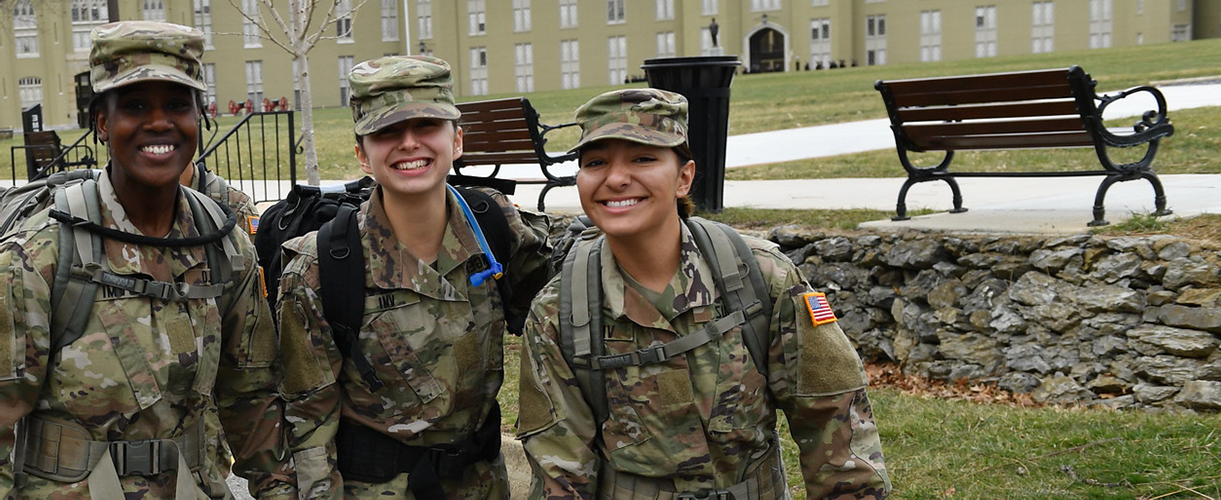 Three female cadets wearing OCP, smiling during a march along Letcher Ave