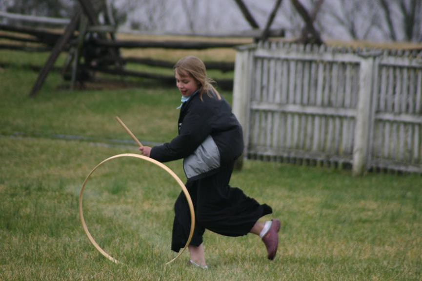 Photo of young girl rolling a hoop