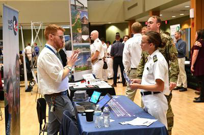 A female cadet talks with a representative from the Peace Corps during a career fair