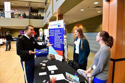 Lt. Col. Ammad Sheikh, director of Career Services, speaks with career fair attendees